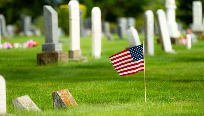American flag placed at a burial site in a cemetery.