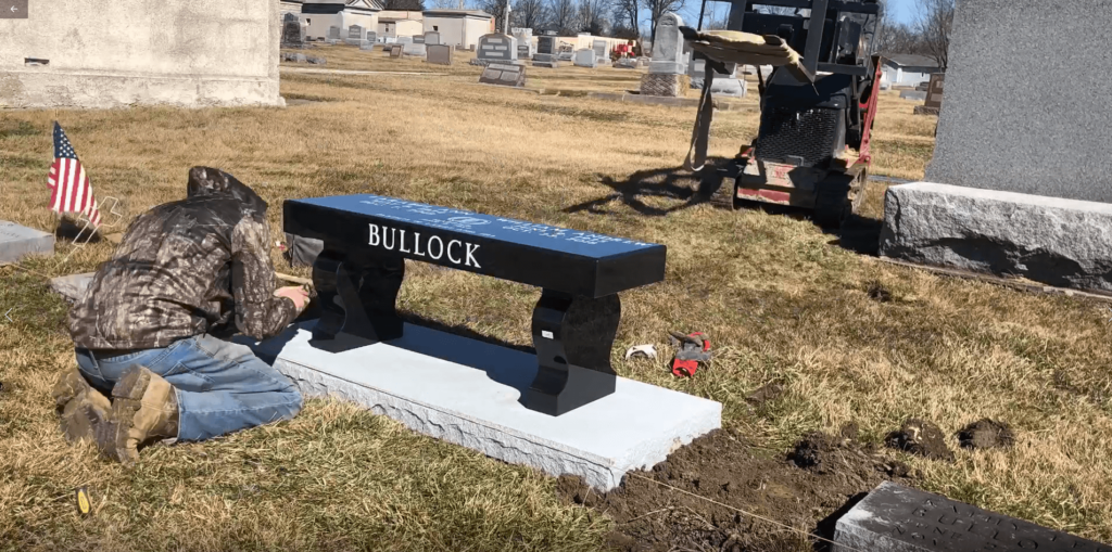 work crew member installing a bench monument